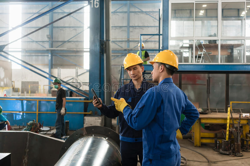 Experts checking information on tablet PC in a modern factory royalty free stock photography