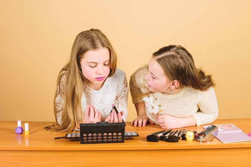 Experts in colour. Adorable small makeup artists using colour cosmetics. Cute little girls applying colour eyeshadow stock images
