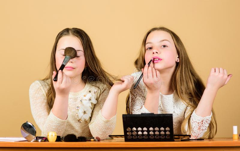 Experts in cosmetics. Cute beauty models wearing facial cosmetics. Little girls applying decorative cosmetics with royalty free stock photos
