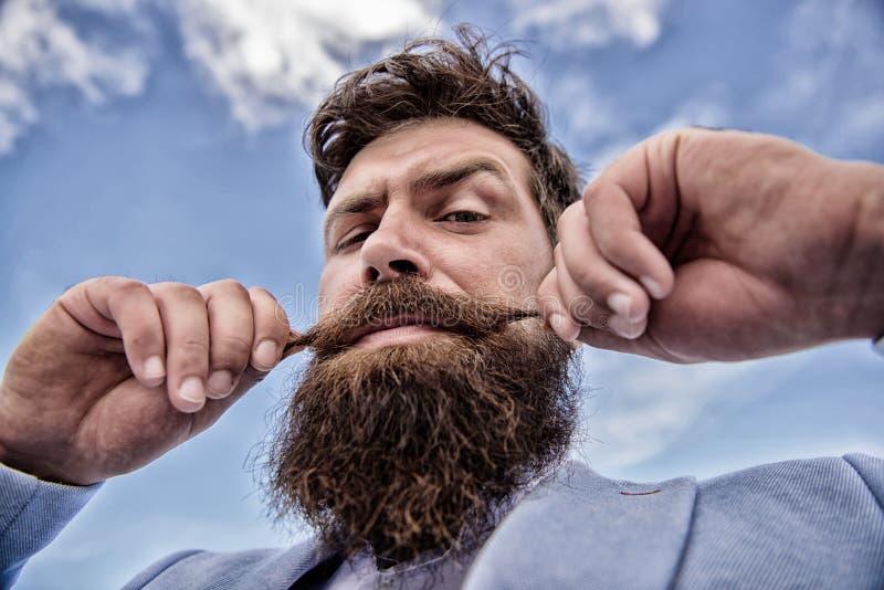 Expertspetsar f?r v?xande och underh?llande mustasch Sk?ggig hipster f?r man som vrider mustaschhimmelbakgrund ultimat royaltyfri fotografi
