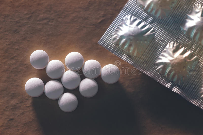 Expired pills on dirty brown background. royalty free stock photography