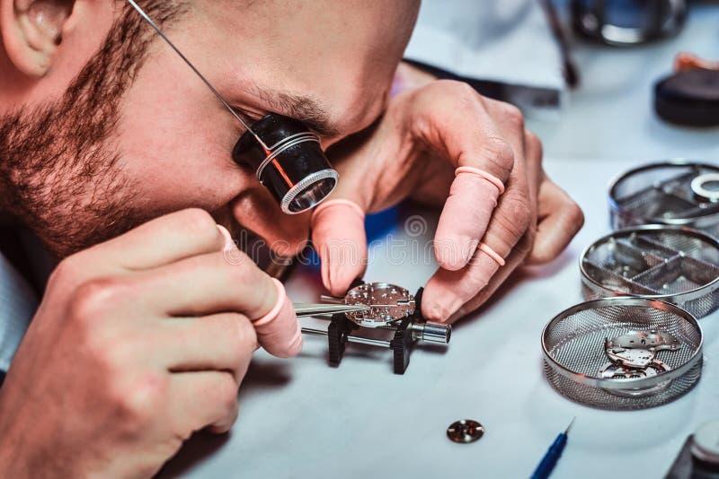 Expirienced clockmaster bevestigt oud horloge voor een klant op zijn het herstellen workshop stock fotografie