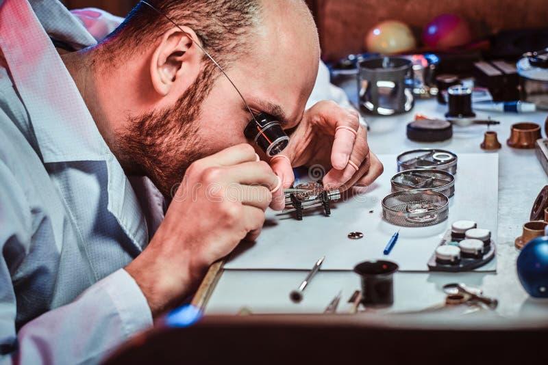 Expirienced clockmaster bevestigt oud horloge voor een klant op zijn het herstellen workshop royalty-vrije stock afbeeldingen