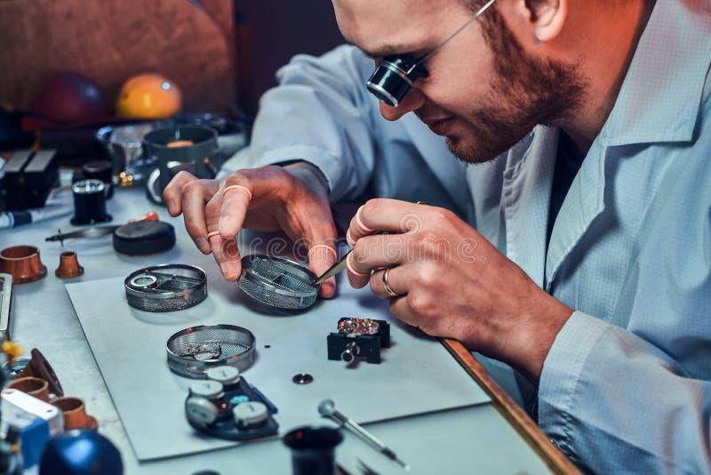 Expirienced clockmaster bevestigt oud horloge voor een klant op zijn het herstellen workshop stock foto's