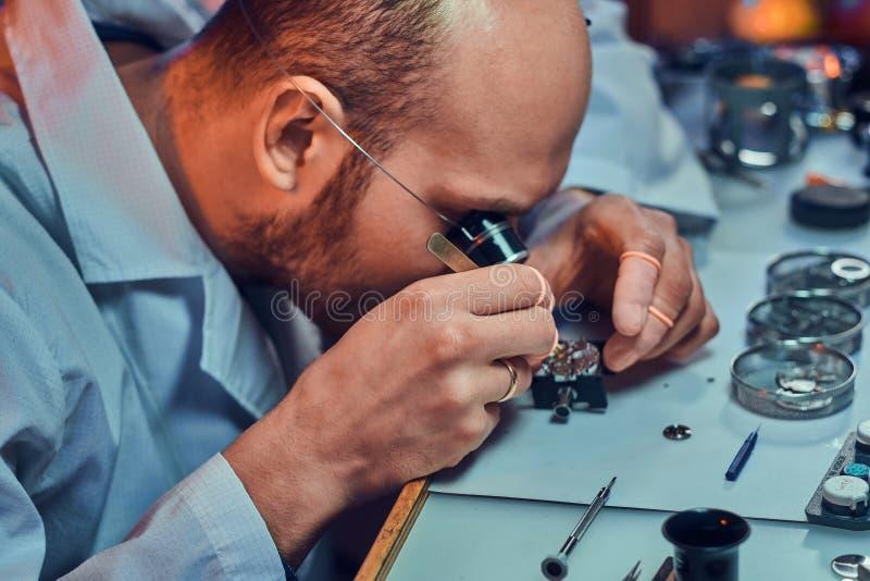 Expirienced clockmaster za?atwia starego zegarek dla klienta przy jego naprawianie warsztatem obrazy royalty free