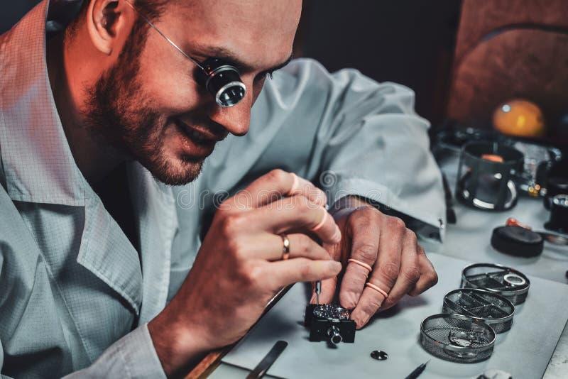 Expirienced clockmaster za?atwia starego zegarek dla klienta przy jego naprawianie warsztatem zdjęcie stock