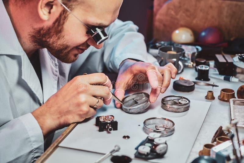Expirienced clockmaster za?atwia starego zegarek dla klienta przy jego naprawianie warsztatem zdjęcia royalty free