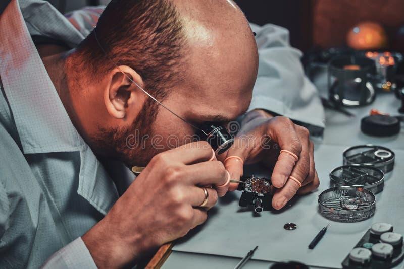 Expirienced clockmaster za?atwia starego zegarek dla klienta przy jego naprawianie warsztatem zdjęcie royalty free