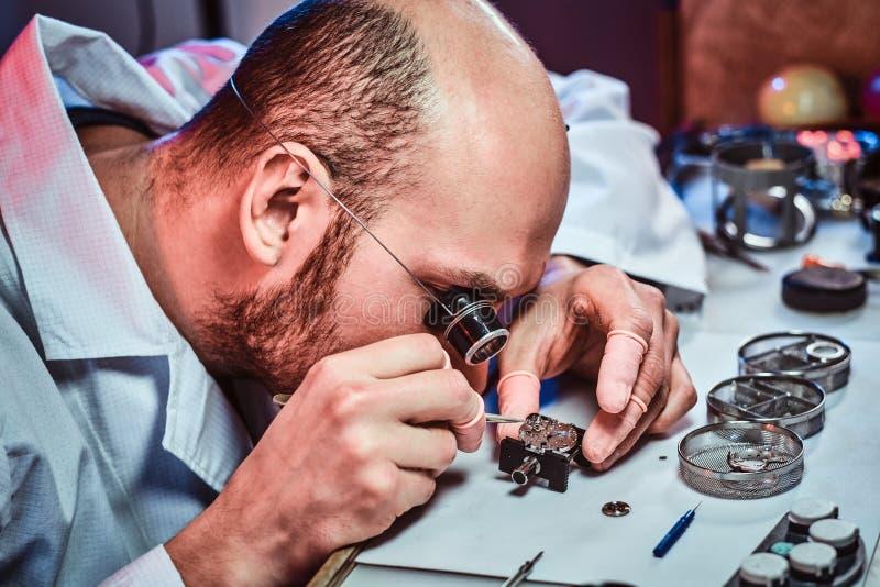 Expirienced clockmaster za?atwia starego zegarek dla klienta przy jego naprawianie warsztatem obraz royalty free
