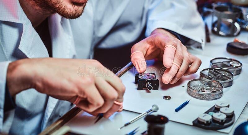 Expirienced clockmaster za?atwia starego zegarek dla klienta przy jego naprawianie warsztatem zdjęcia stock