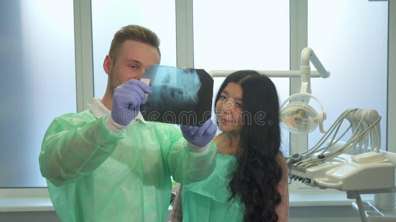 Explaines del dentista al paciente algo en radiografía foto de archivo libre de regalías
