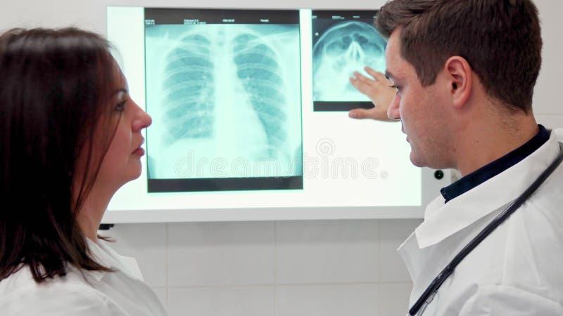 Explaines masculinos do doutor algo no raio X a seu colega fêmea foto de stock royalty free