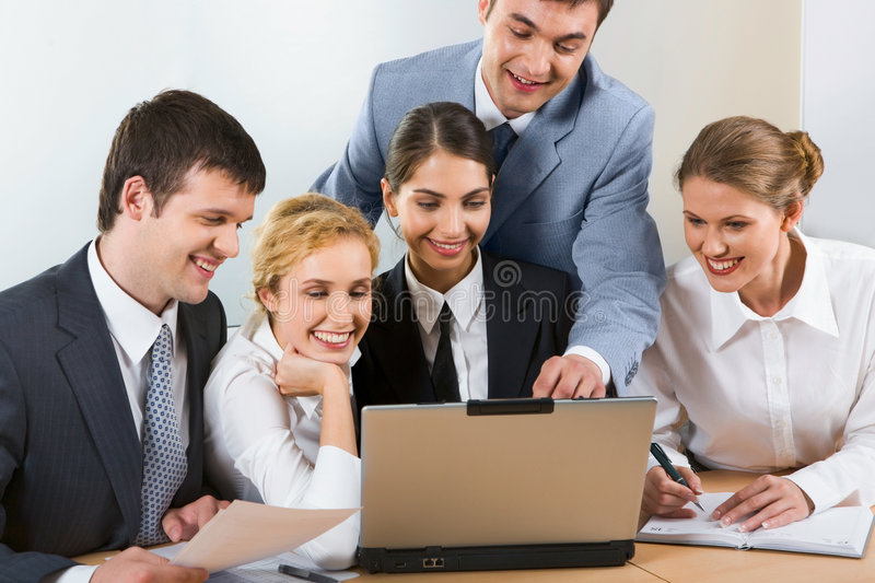 Explaining. Group of five young businesspeople gathered together around the laptop discussing interesting question
