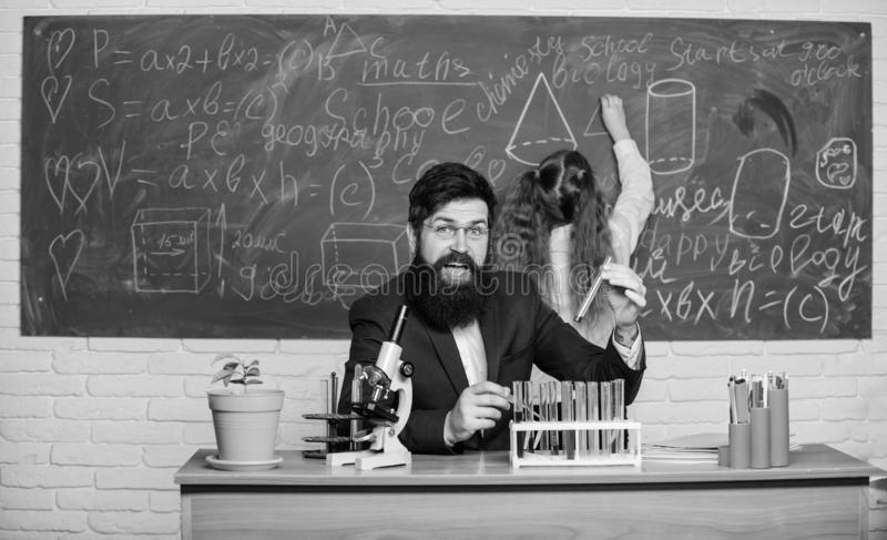 Explaining biology to children. Man bearded teacher work with microscope and test tubes in biology classroom. Biology stock photo