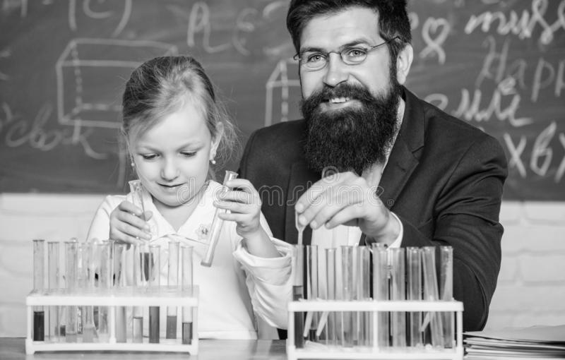 Explaining chemistry to kid. How to interest children study. Fascinating chemistry lesson. Man bearded teacher and pupil stock photos
