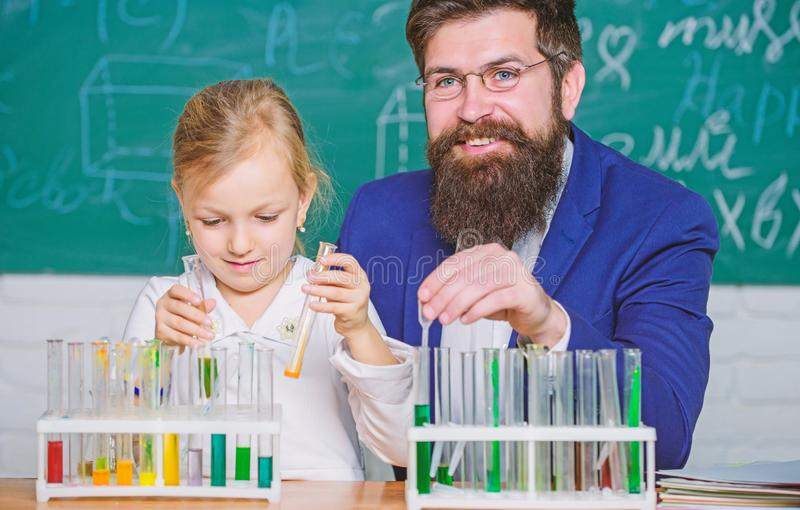 Explaining chemistry to kid. How to interest children study. Fascinating chemistry lesson. Man bearded teacher and pupil stock image
