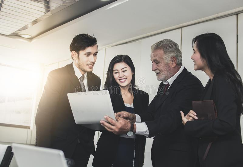 Explaining and discussing concept, Happy and kind manager talking with staffs by holding laptop and introducing his partners royalty free stock image