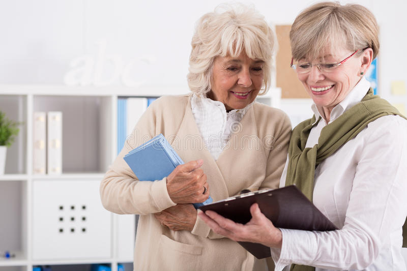 Explaining something to classmate. Two elderly students are studying notes from a lecture royalty free stock image