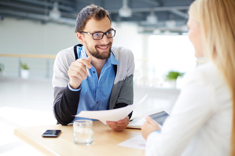 Explaining viewpoint. Smiling businessman with paper talking to his colleague at meeting royalty free stock images