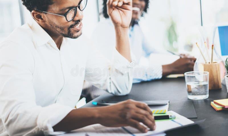 Explaning Geschäftsaufgabe des Schwarzafrikanermitarbeiters im Konferenzzimmer Zwei junge Unternehmer, die in einem modernen zusa stockfotos