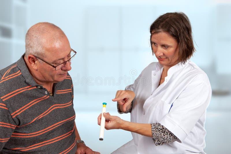 Explicação da enfermeira como usar a pena da insulina fotografia de stock royalty free