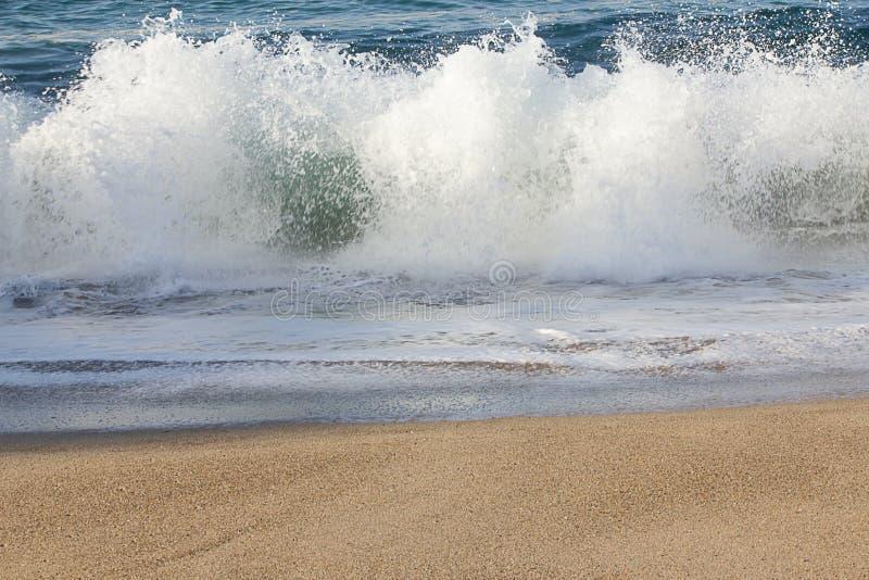 exploderende golfplons met het schuimen backsplash op zandig strand royalty-vrije stock afbeeldingen