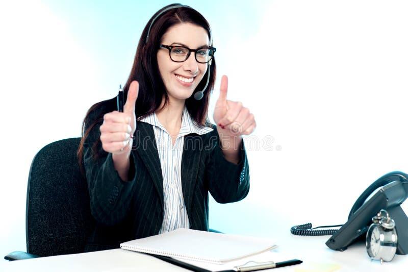 Exploitant de centre serveur d'appel faisant des gestes de doubles pouces vers le haut image stock