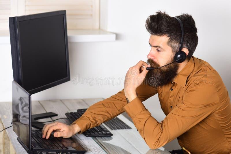Exploitant online Gebaarde mens die in bureau werken Call centreexploitant op het werk Mens met lange baard en hoofdtelefoons royalty-vrije stock foto