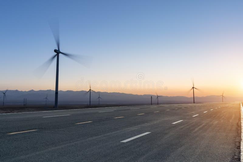 Exploração agrícola da estrada e de vento no crepúsculo imagens de stock