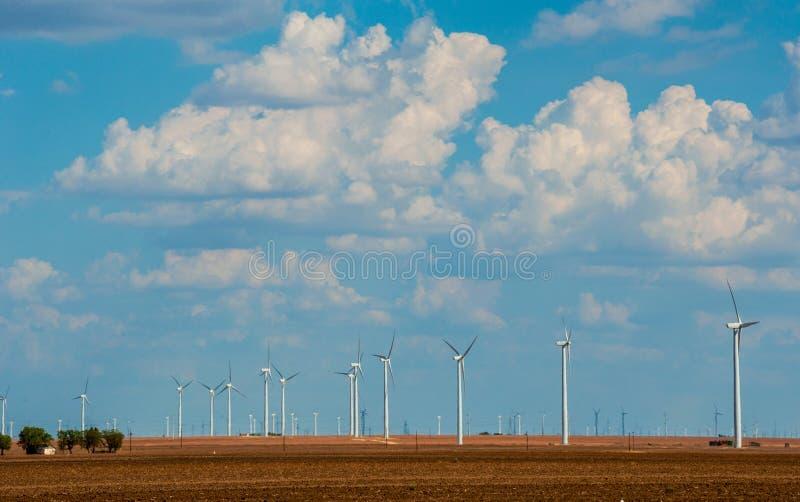Exploração agrícola da turbina eólica em Texas Cumulus Clouds Building ocidental no dia de verão agradável imagens de stock
