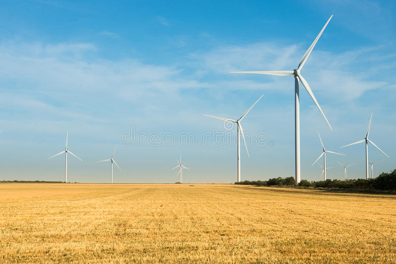 Exploração agrícola das turbinas de vento Moinho selvagem no campo com céu azul Poder e energia fotos de stock royalty free