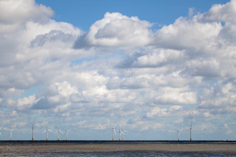 Exploração agrícola de vento a pouca distância do mar no horizonte abaixo do céu nebuloso fotografia de stock