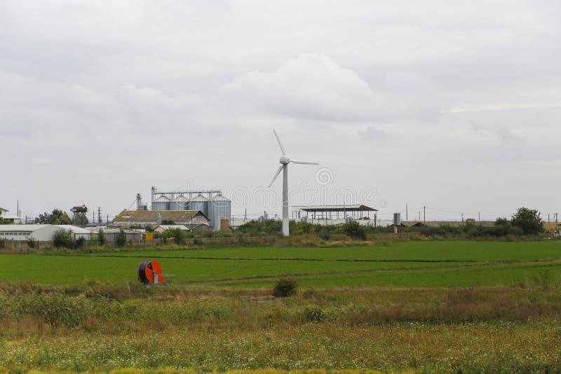 Exploração agrícola moderna equipada com a turbina eólica foto de stock