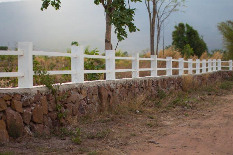 Exploração agrícola rural da cerca concreta branca imagem de stock royalty free