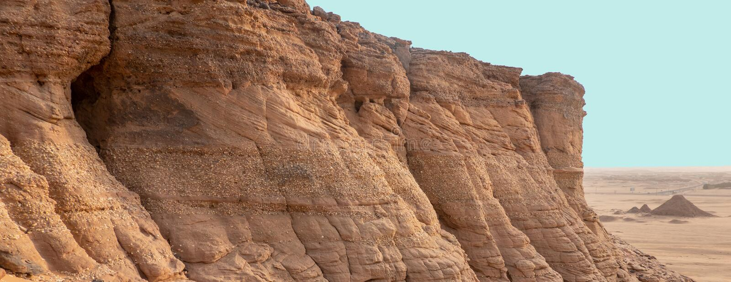 Exploración en una roca de la piedra arenisca con una capa de la cuesta y bancos intermedios del conglomerado, depositados cerca  imagen de archivo