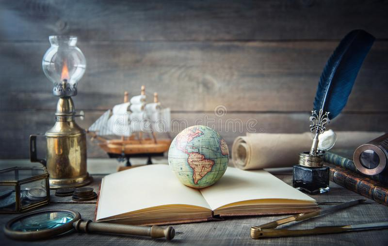 Exploración y fondo náutico del grunge del tema Globo, telescopio, divisor, monedas viejas, cáscara, mapa, libro, reloj de arena, fotos de archivo