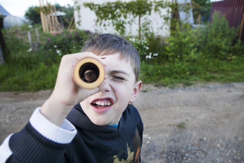 Explorador curioso pequeno, menino que olha céus através do telescópio pequeno do cartão fotos de stock royalty free