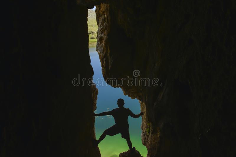 Explorador da caverna que olha para fora da caverna imagem de stock royalty free