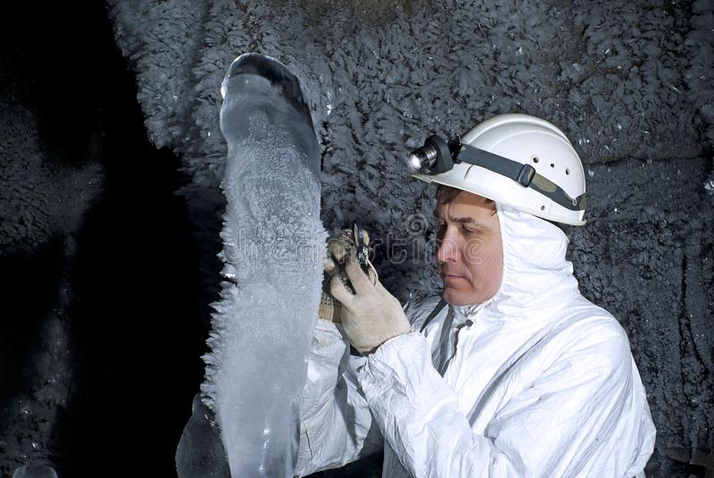 Explorador de la cueva en la cueva de hielo imagenes de archivo