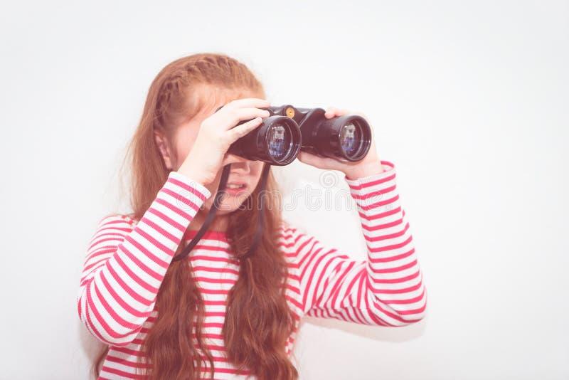 Explorador de la niña que mira a través de los prismáticos fotos de archivo