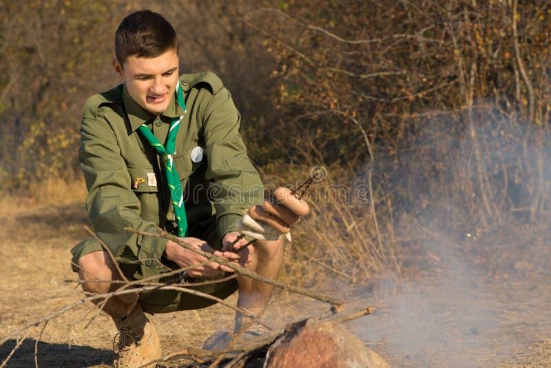 Explorador de los jóvenes que cocina su almuerzo sobre un fuego imagenes de archivo