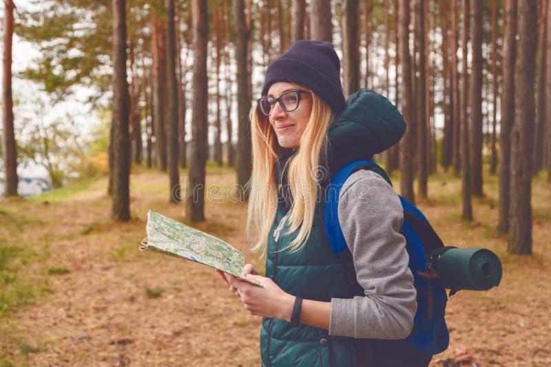 Explorador de sexo femenino con el mapa al aire libre en el bosque en otoño fotos de archivo