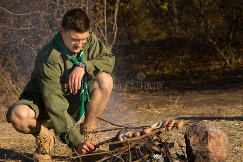 Explorador de sexo masculino joven Grilling Sausages en el campo fotografía de archivo