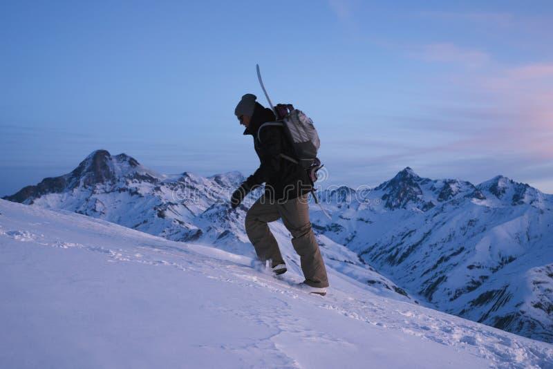 Explorador do homem com um snowboard atrás do seu escalada traseira na montanha alta foto de stock