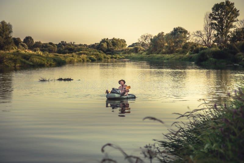 Explorador do viajante que viaja no barco de rio durante a expedição da aventura do curso no por do sol foto de stock