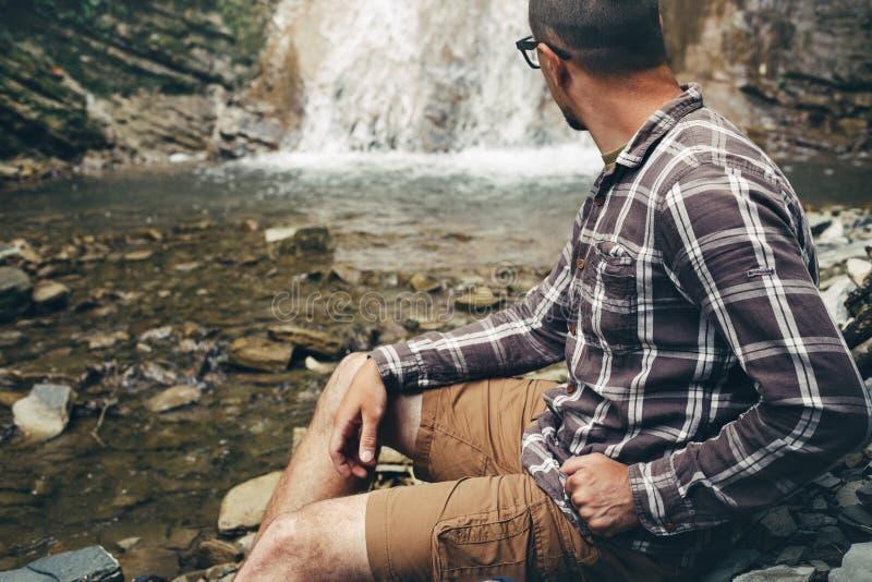 Explorador Sitting And Looks do viajante na cachoeira Curso que caminha o conceito do estilo de vida da experiência do destino imagem de stock royalty free