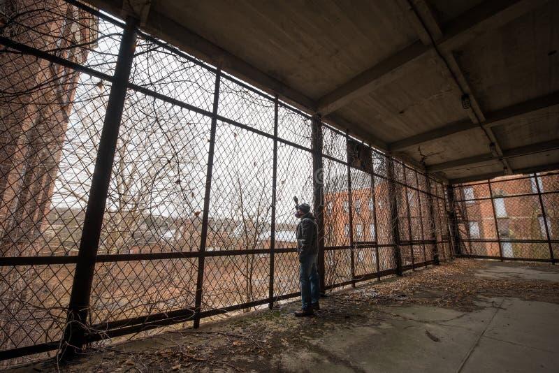 Explorador urbano que mira fuera de una jaula imagenes de archivo