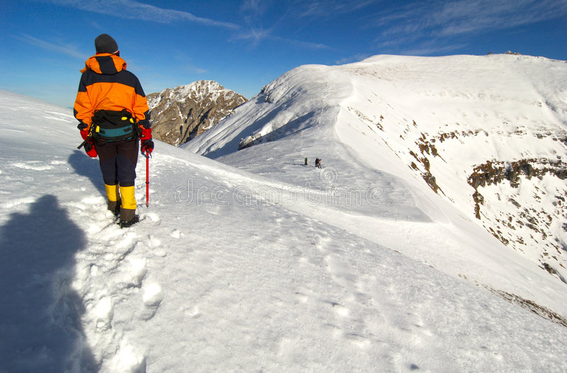 Exploration. An adventurer stands along a snow-covered mountain range, looking into the distance as other adventurers trek on ahead stock photography
