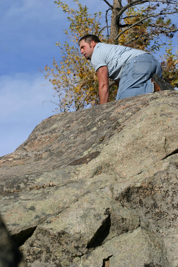 Explore. Young man on top of a large boulder looking intently off into the distance royalty free stock image
