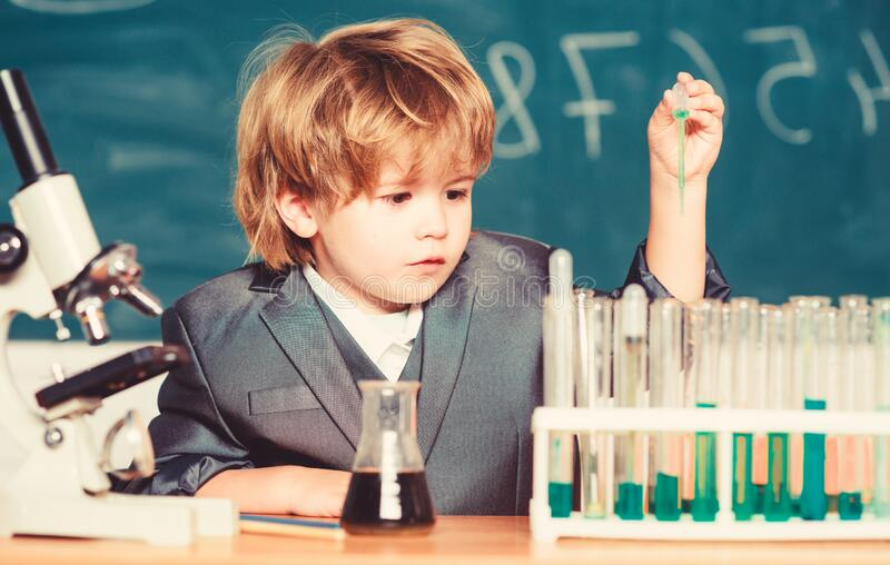 Explore biological molecules. Toddler genius baby. Boy near microscope and test tubes in school classroom. Technology stock photos